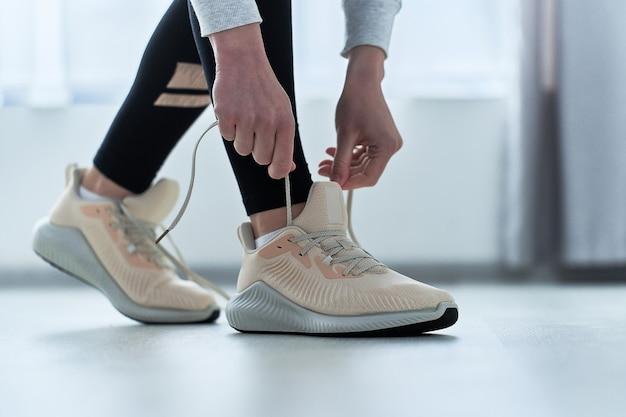 Fitness kobieta wiąże sznurowadła na beżowych tenisówkach i przygotowuje się do biegania i treningu. uprawiaj sport i bądź wysportowany. sportowcy ze zdrowym sportowym stylem życia