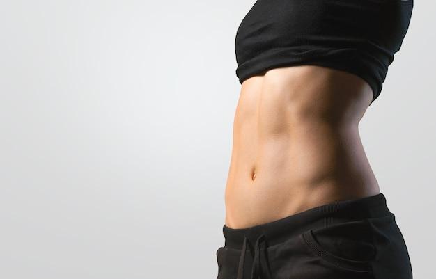Fitness kobieta wyświetlono abs i płaski brzuch, na białym tle. wysportowana dziewczyna w kształcie brzucha