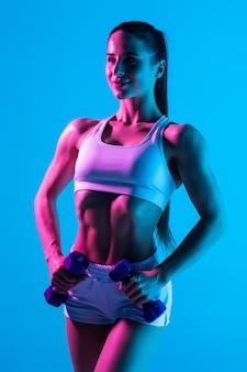 Fitness kobieta z hantle dopasowanie szczupłe ciało abs na białym tle na niebieskim tle światła