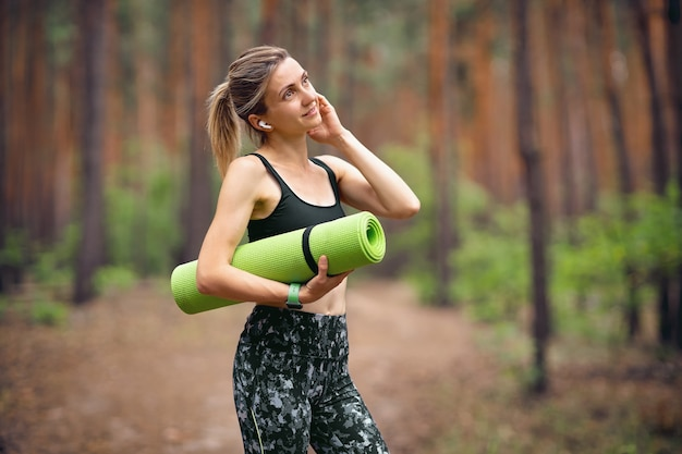 Fitness kobieta z matą do jogi w parku rozmawia przez telefon lub słucha muzyki za pomocą słuchawek bezprzewodowych.