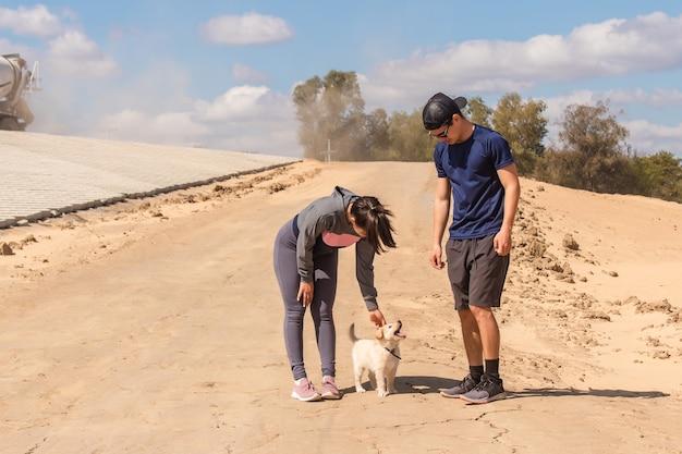 Fitness kobieta z partnerem pieszczoty swojego małego psa na piasku.
