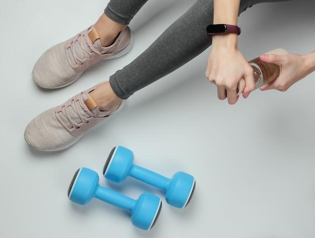 Fitness, koncepcja sportu. kobiece nogi ubrane w legginsy i trampki siedzą na białym tle z butelką wody do treningu i hantlami. widok z góry