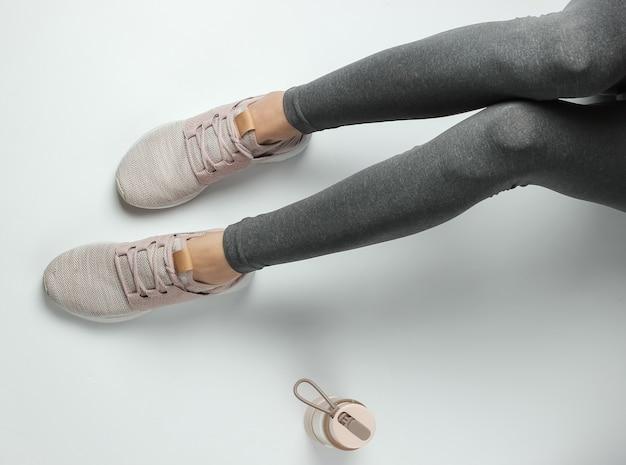 Fitness, koncepcja sportu. kobiece nogi ubrane w legginsy i trampki siedzą na białym tle z butelką wody do treningu. widok z góry