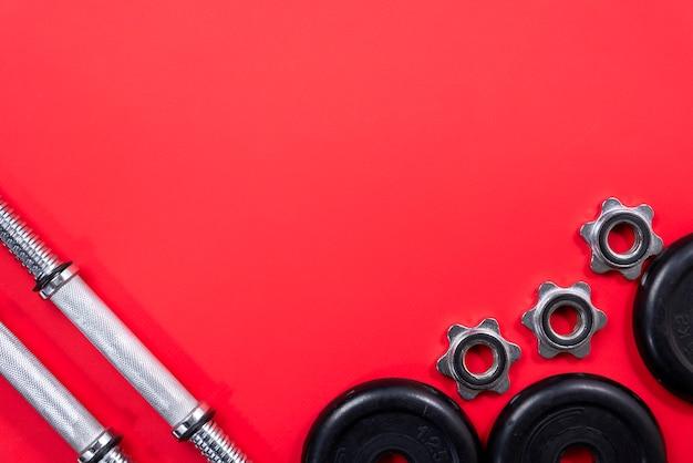 Fitness lub kulturystyka. sprzęt sportowy na czerwonym tle, widok z góry