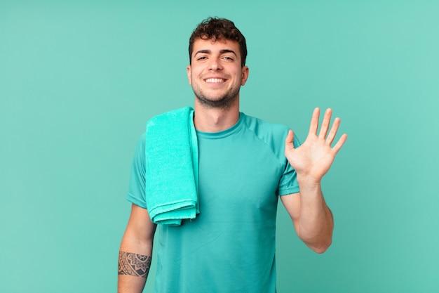 Fitness man uśmiechający się radośnie i radośnie, machający ręką, witający i witający cię lub żegnający się