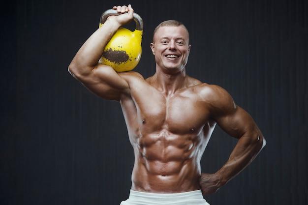 Fitness mężczyzna pompowania mięśni z kettlebell