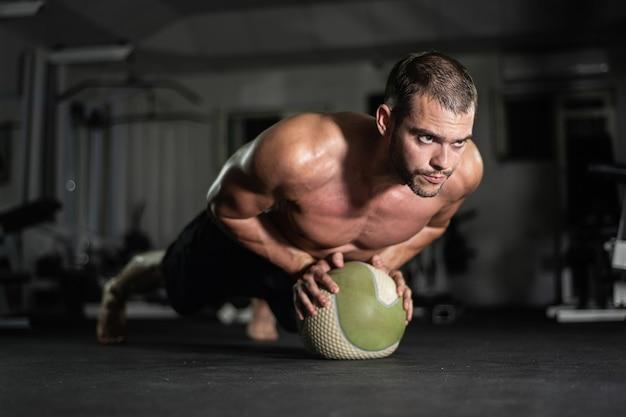 Fitness mężczyzna robi pompki na piłkę