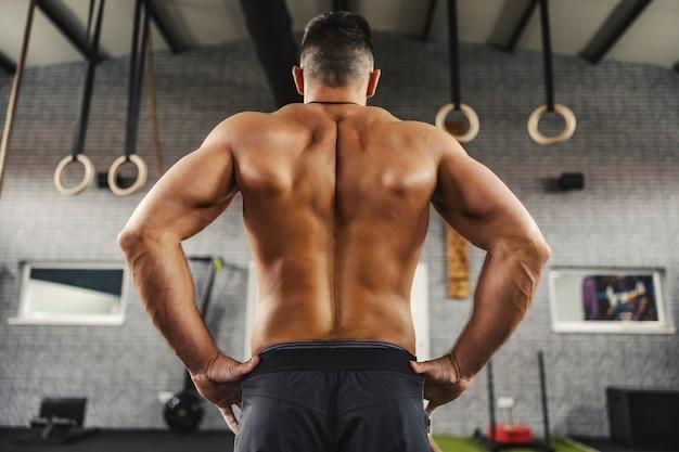 Fitness mężczyzna stoi na środku siłowni bez koszuli