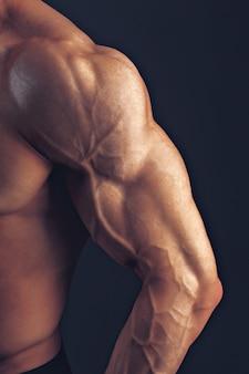 Fitness mężczyzna tło bark biceps mięśnie piersiowe triceps kulturysta na ciemnym tle