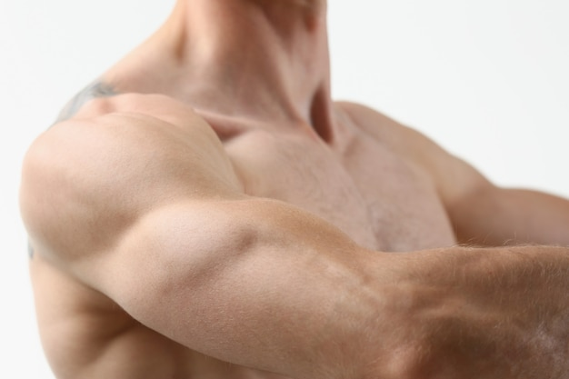 Fitness mężczyzna tło ramię biceps mięśnie piersiowe kulturysta triceps na szarym tle pokazuje formę fizyczną do zajęć na siłowni
