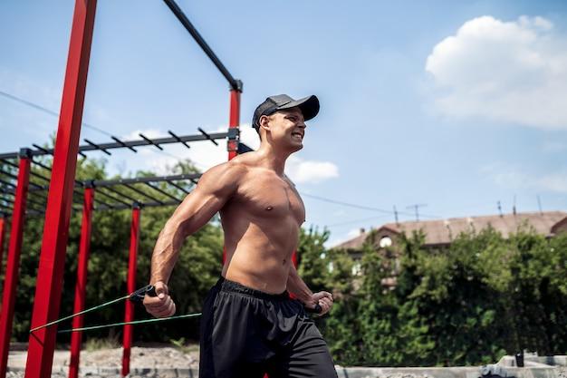 Fitness mężczyzna trening klatki piersiowej z opaskami na podwórku siłowni ulicy
