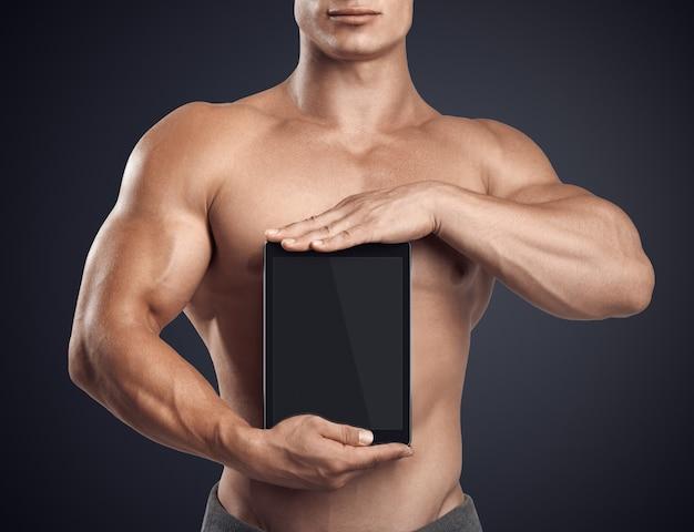 Fitness mężczyzna trzyma pionowo cyfrowy tablet z pustego ekranu