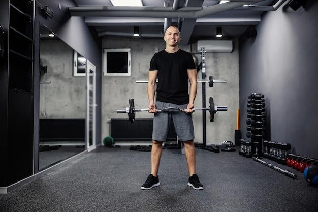Fitness mężczyzna w odzieży sportowej i dobrej kondycji fizycznej w odizolowanej sali gimnastycznej