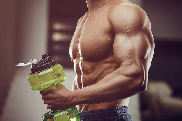 Fitness mężczyzna w wodzie pitnej siłownia po treningu. fitness i kulturystyka zdrowe tło.