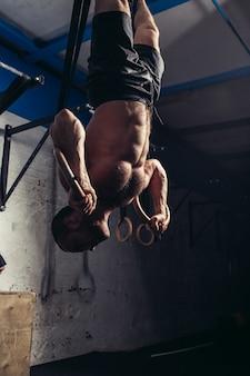 Fitness mężczyzna wisi do góry nogami na pierścienie gimnastyczne