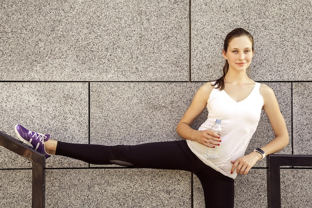 Fitness piękna kobieta z piegami na twarzy wody pitnej i pocenie się po ćwiczeniach w mieście. lekkoatletka po treningu. patrząc na aparat i uśmiechając się.