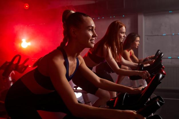 Fitness razem na rowerach. młodzi przyjaciele pedałują na rowerze stacjonarnym na siłowni w oświetlonej czerwonymi neonami przestrzeni. ćwiczenia cardio na maszynie