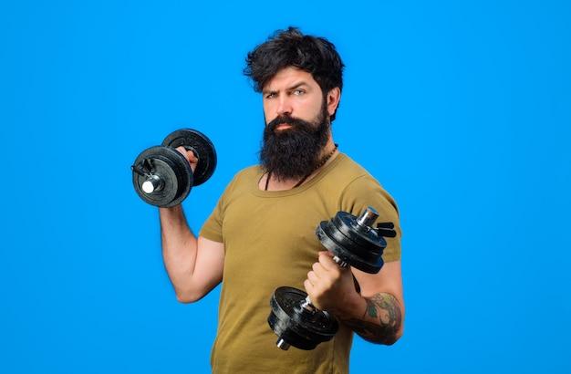 Fitness siłacz trening z hantlami brodaty mężczyzna ćwiczenia z hantlami przystojny sportowiec mężczyzna