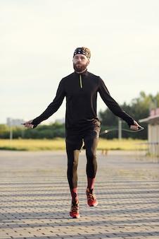 Fitness sport człowiek skaczący z skakanką na zewnątrz