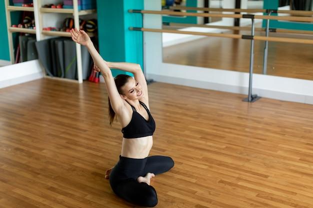 Fitness, sport i pojęcie zdrowego stylu życia - kobieta robi ćwiczenia jogi w studio.