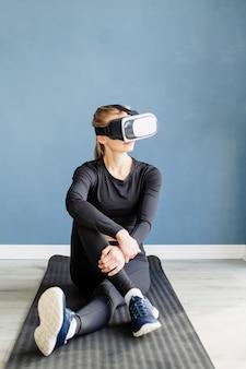 Fitness, sport i technologia. młoda kobieta lekkoatletycznego w okularach wirtualnej rzeczywistości siedzi na macie fitness