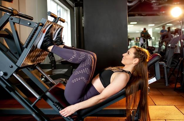 Fitness, sport, kulturystyka, ćwiczenia i koncepcja ludzi - młoda kobieta, wyginanie mięśni na maszynie prasy nogi w siłowni