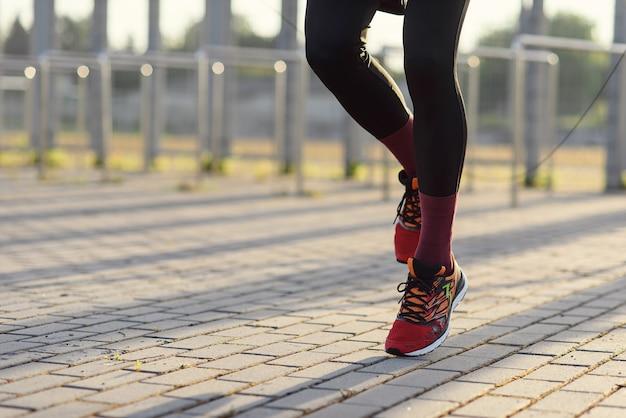 Fitness sport ludzie ćwiczący i koncepcja stylu życia człowiek skaczący ze skakanką na zewnątrz