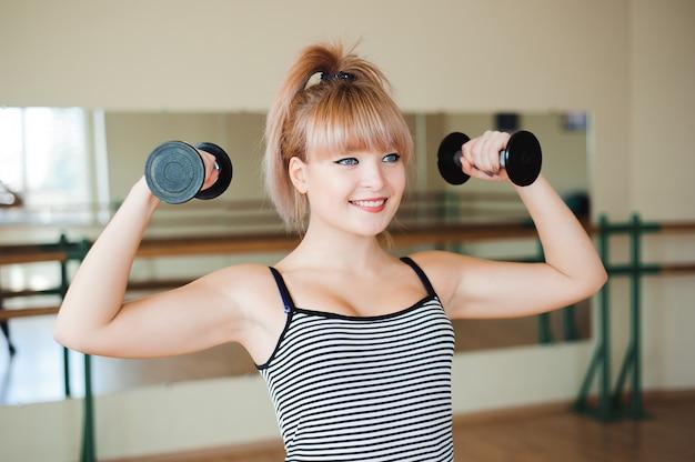 Fitness, sport, styl życia - atrakcyjna młoda kobieta robi ćwiczenia siłowe na siłowni.