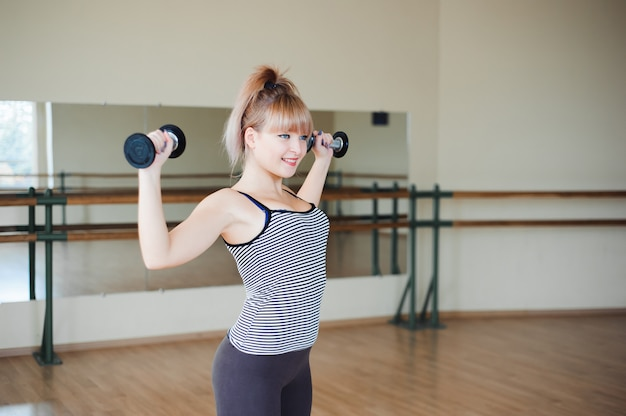 Fitness, sport, styl życia - atrakcyjna młoda kobieta robi ćwiczenia siłowe na siłowni