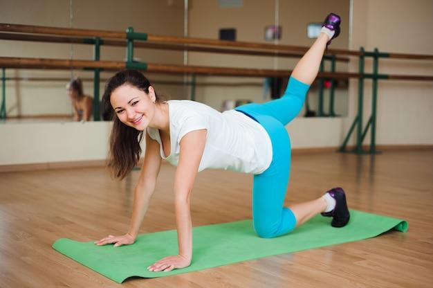 Fitness, sport, styl życia - szczęśliwe kobiety noszą w body robiąc ćwiczenia na siłowni.
