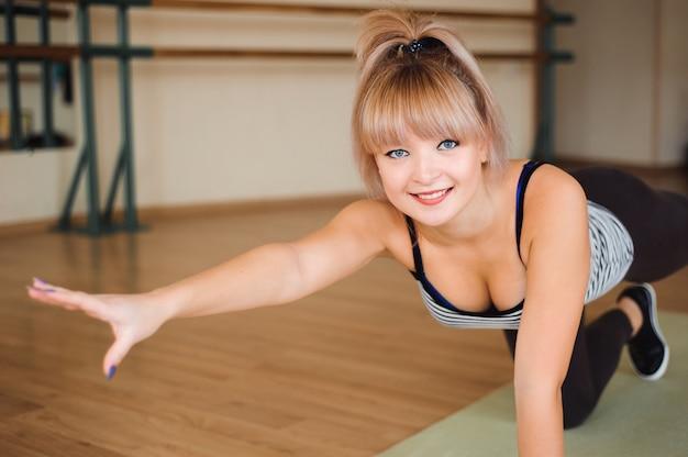 Fitness, sport, styl życia - szczęśliwe kobiety noszą w body robiąc ćwiczenia na siłowni