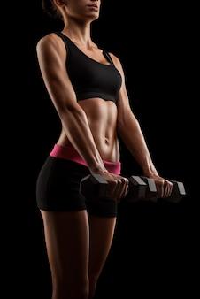 Fitness sportowa kobieta w treningu pompowania mięśni z hantlami młode sportowe ciało kobiety fitness