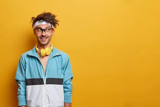 Fitness sportowy facet w dobrym humorze, patrzy na bok z motywacją, lubi trening i sport, słucha muzyki w słuchawkach podczas treningu, ubrany w aktywny strój, kopiuje przestrzeń na żółtej ścianie