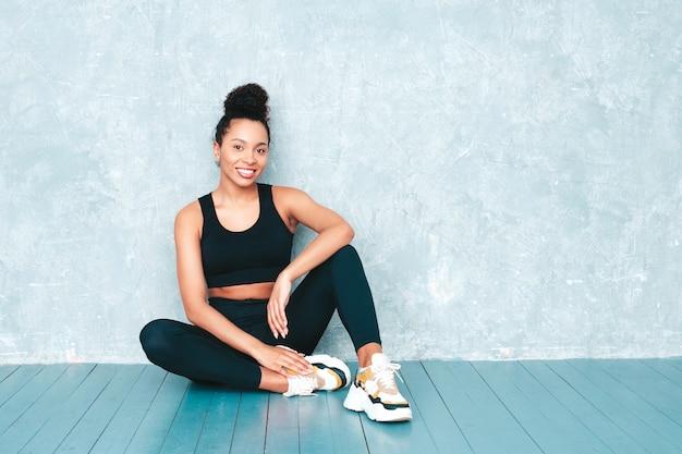 Fitness uśmiechnięta kobieta w sportowej odzieży z fryzurą afro loki