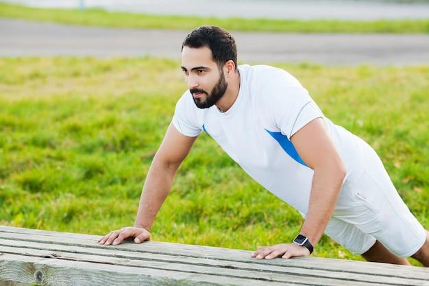 Fitness w parku. młody i sportowy mężczyzna trenujący na zewnątrz w odzieży sportowej. sport, zdrowie, lekkoatletyka.
