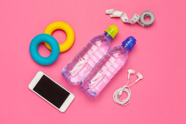 Fitness z butelką wody, telefon komórkowy ze słuchawkami