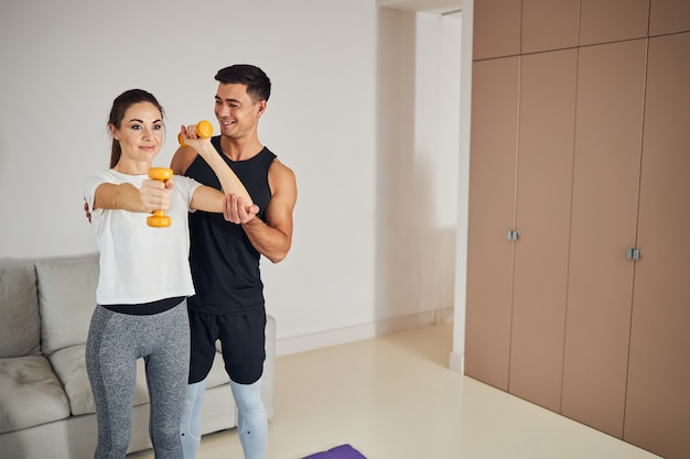Fitnesswise uśmiechnięta para robi razem trening w domu