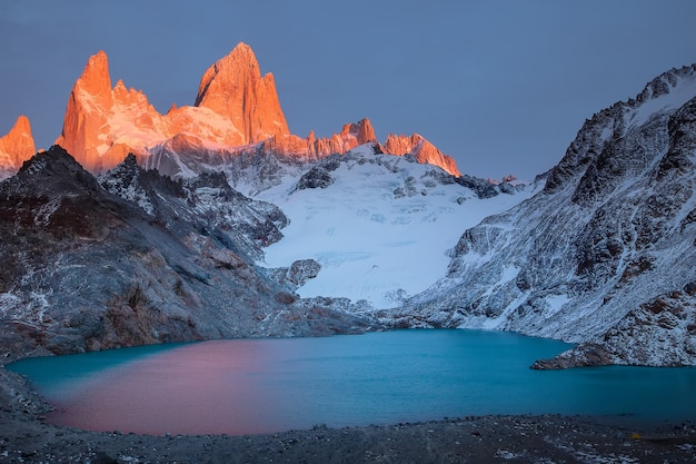 Fitzroys czerwony płonący szczyt i jezioro o wschodzie słońca w parku narodowym los glaciares w argentynie patagonia