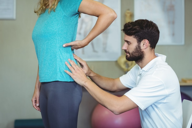 Fizjoterapeuta bada plecy kobiety