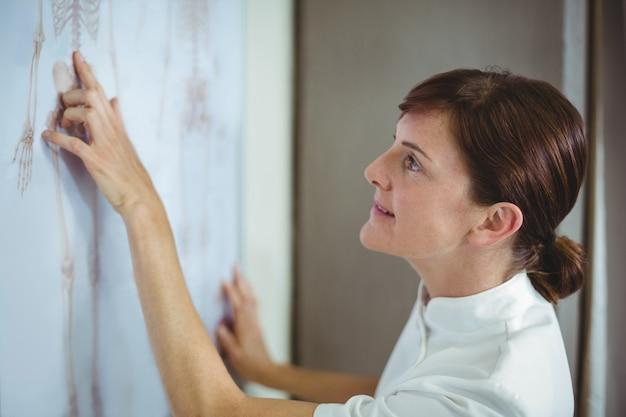 Fizjoterapeuta bada szkielet szkic na białej tablicy