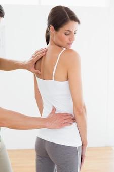 Fizjoterapeuta, badając womans z powrotem w biurze medycznym