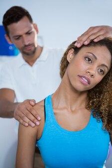 Fizjoterapeuta daje masaż szyi pacjentce