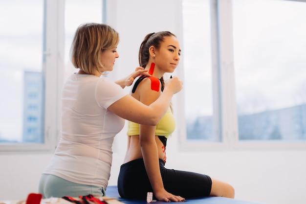 Fizjoterapeuta kładąc taśmę kinesio na ramieniu i szyi kobiety