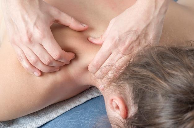Fizjoterapeuta, kręgarz daje masaż pacjentowi.