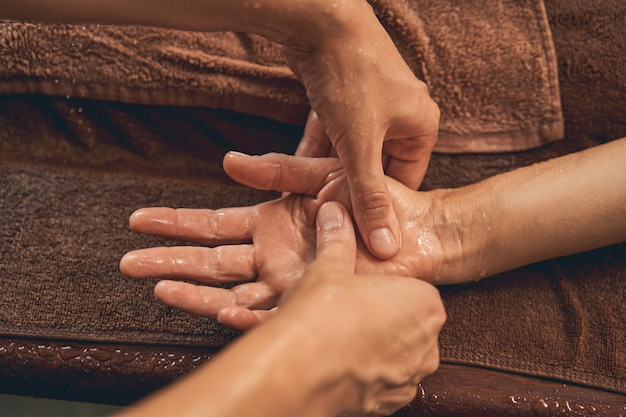 Fizjoterapeuta masujący dłoń mężczyzny w luksusowym kurorcie spa