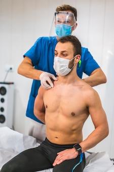 Fizjoterapeuta masujący pacjentowi obojczyk. fizjoterapia ze środkami ochronnymi przeciwko pandemii koronawirusa, covid-19. osteopatia, terapeutyczny chiromasaż