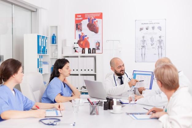 Fizjoterapeuta mężczyzna lekarz trzymający schowek w rękach przedstawiający ekspertyzy zdrowotne wyjaśniające leczenie chorób omawiające diagnostykę choroby disease