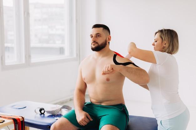 Fizjoterapeuta nakładający taśmę kinesio pacjentom zranionym w ramię
