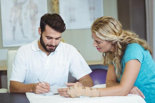 Fizjoterapeuta pisze raport obok pacjenta