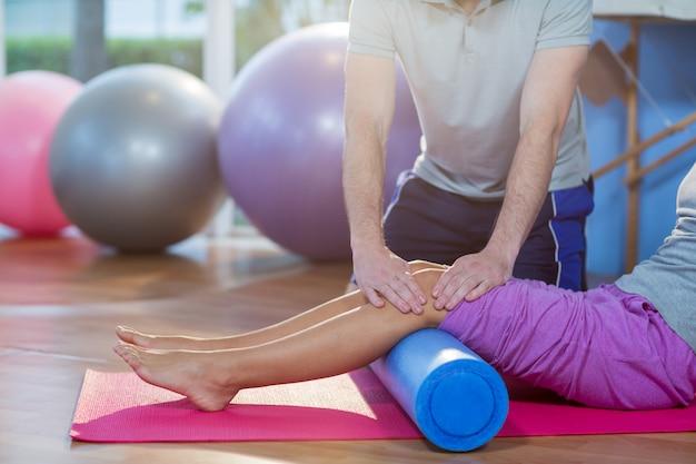 Fizjoterapeuta pomaga kobiecie podczas ćwiczeń na macie do ćwiczeń